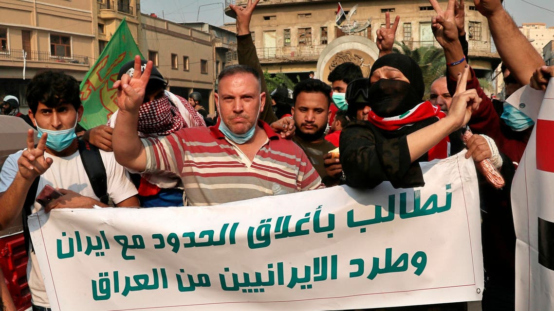 """Iraqi Anti-government protesters hold a banner with Arabic that reads, """"We demand the expulsion of Iranians from Iraq and the closure of the border with Iran"""" during ongoing protests in Baghdad, Iraq, Friday, Nov. 29, 2019.(AP)"""