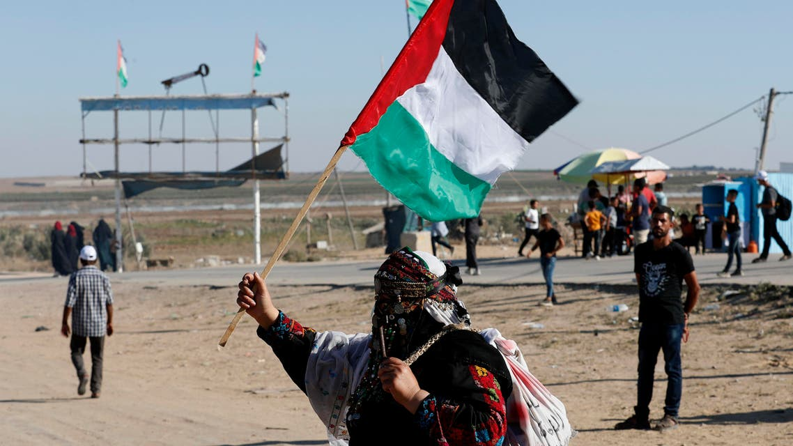 In this Sept. 25, 2019 photo, a Palestinian woman waves a national flag during a alternative protest organized by activist Ahmed Abu Artima near the separation fence between the Gaza Strip and Israel, east of Gaza City. (AP)