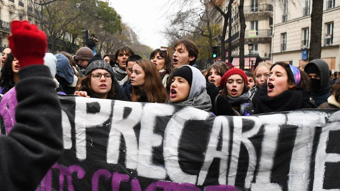 Protesters hold a banner during a demonstration against the pension overhauls, on Place de la Nation in Paris, on December 5, 2019, as part of a national general strike. (AFP)