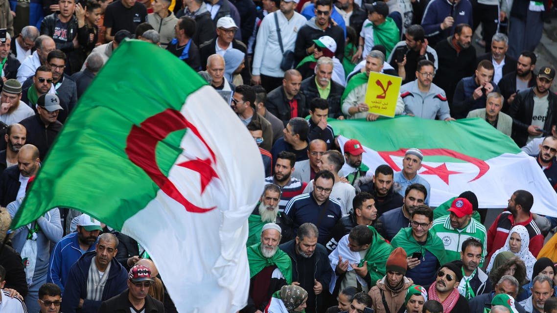 Demonstrators carry national flags during a protest to demand that a presidential election next month be cancelled until the old ruling guard step aside and the army quit politics, in Algiers. (Reuters)