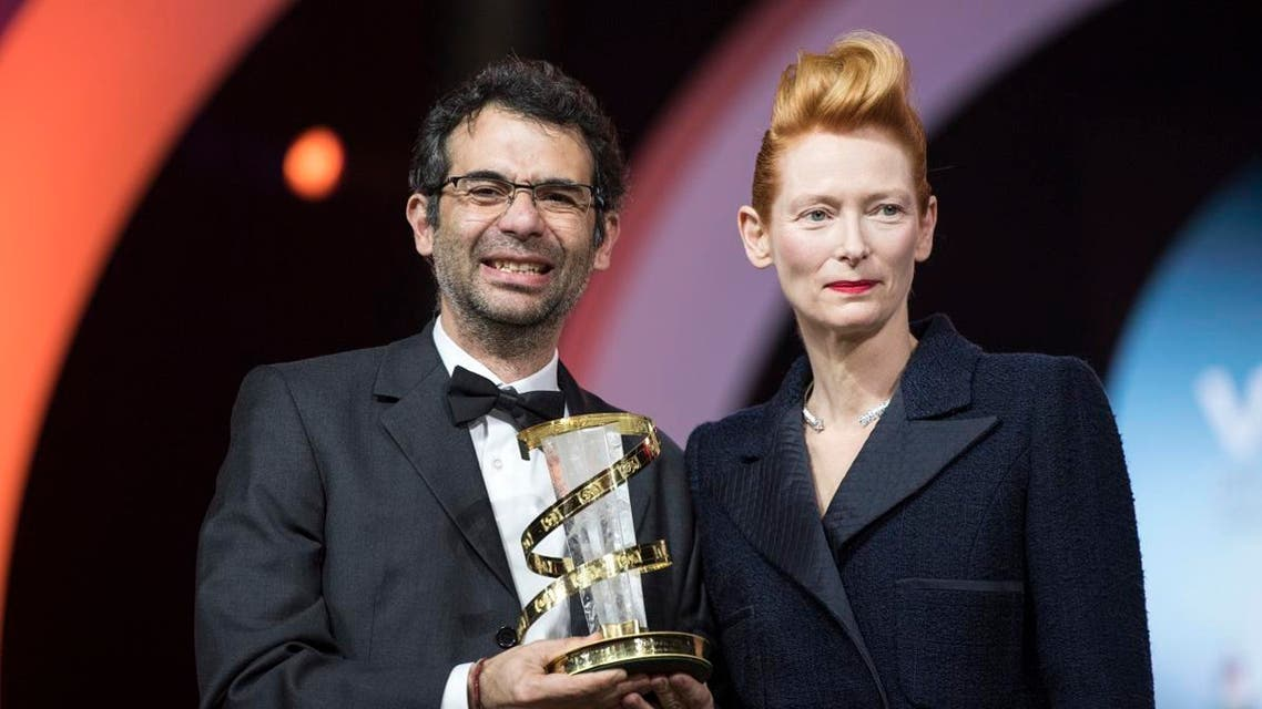 """Colombian director Nicolas Rincon Gille (L) stands with British actress Tilda Swinton as he holds his trophy of the """"Etoile d'or"""" on December 7, 2019, in Marrakech. (AFP)"""