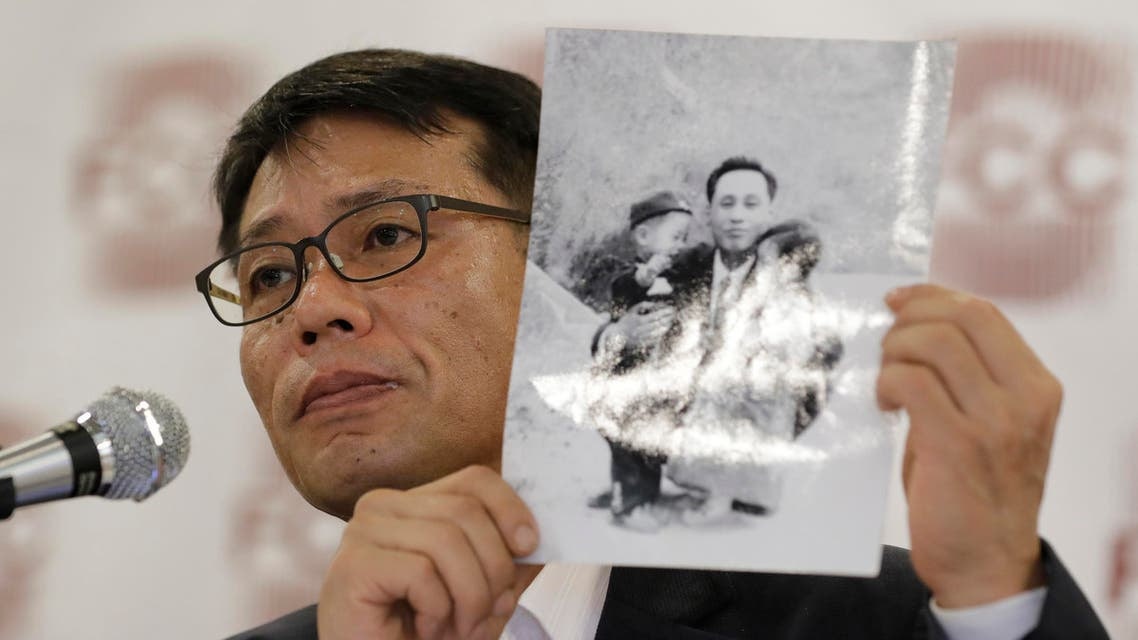 In this May 8, 2018, photo, South Korean Hwang In-cheol, the son of a broadcast journalist whose flight was hijacked by a North Korean operative nearly 50 years ago, holds a photo showing himself with his father, during a press conference in Seoul, South Korea. (AP)
