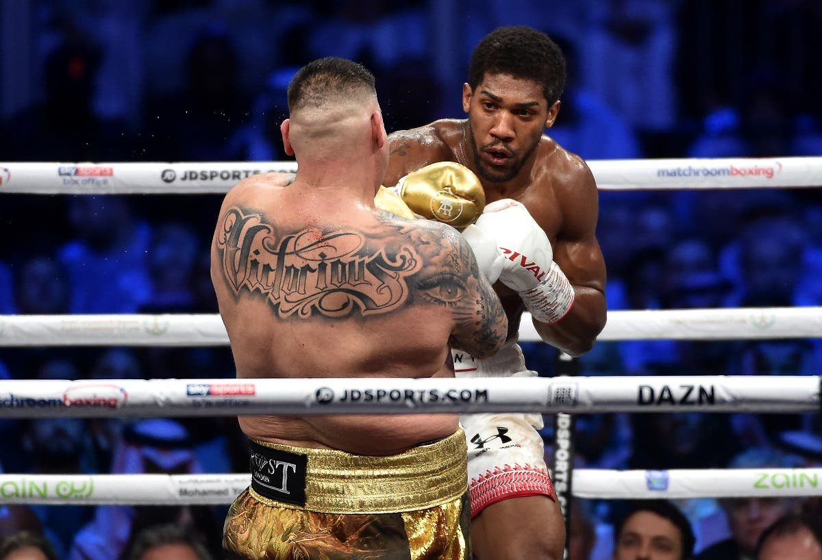 "British boxer Anthony Joshua (white trunks) competes with Mexican-American boxer Andy Ruiz Jr (golden trunks) during the heavyweight boxing match in Diriya, near the Saudi capital Riyadh, dubbed ""Clash on the Dunes."" (AFP)"