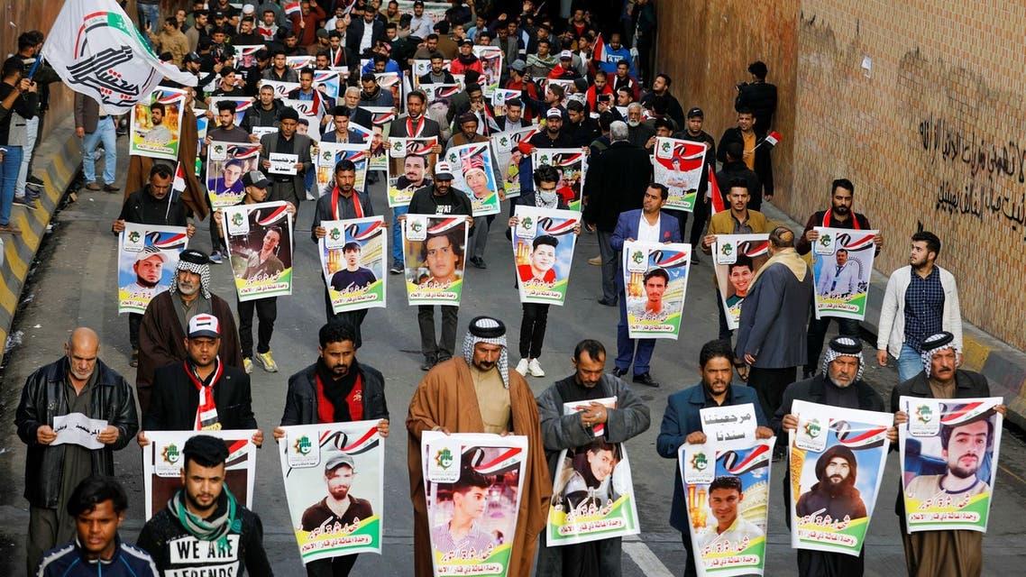 حمل صور المتظاهرين الذين سقطوا في بغداد في الناصرية (فرانس برس)