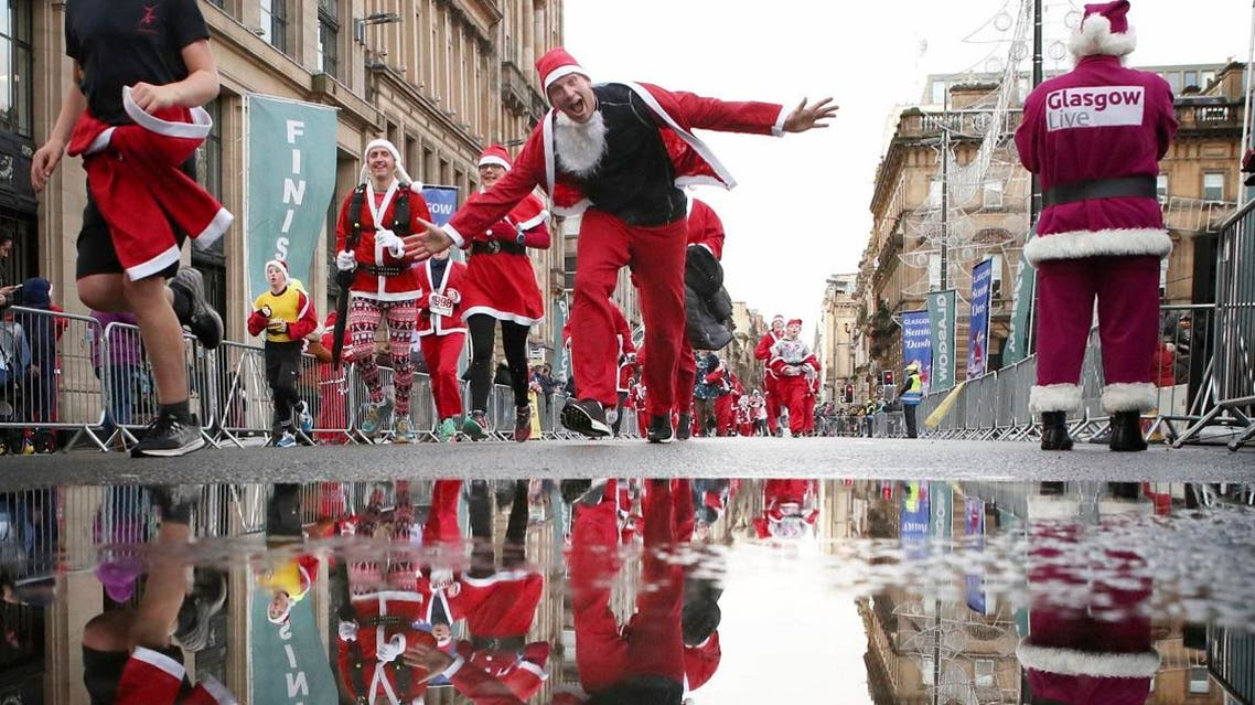 Participants run in Glasgow's annual Christmas Santa dash through the city center, in Glasgow, Scotland. (AP)