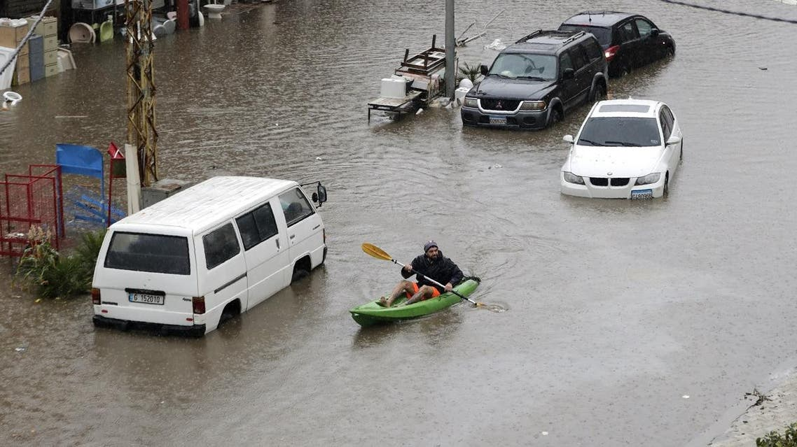A Lebanese man uses a canoe as means of transportation on a flooded road due to heavy rain, at the southern entrance of the capital Beirut on December 9, 2019. (AFP)