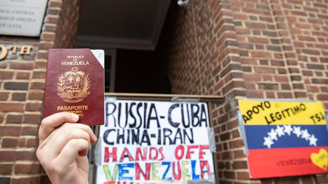 A woman holds up a Venezuelan passport in front of the Venezuelan embassy in Washington DC. (File photo: AFP)