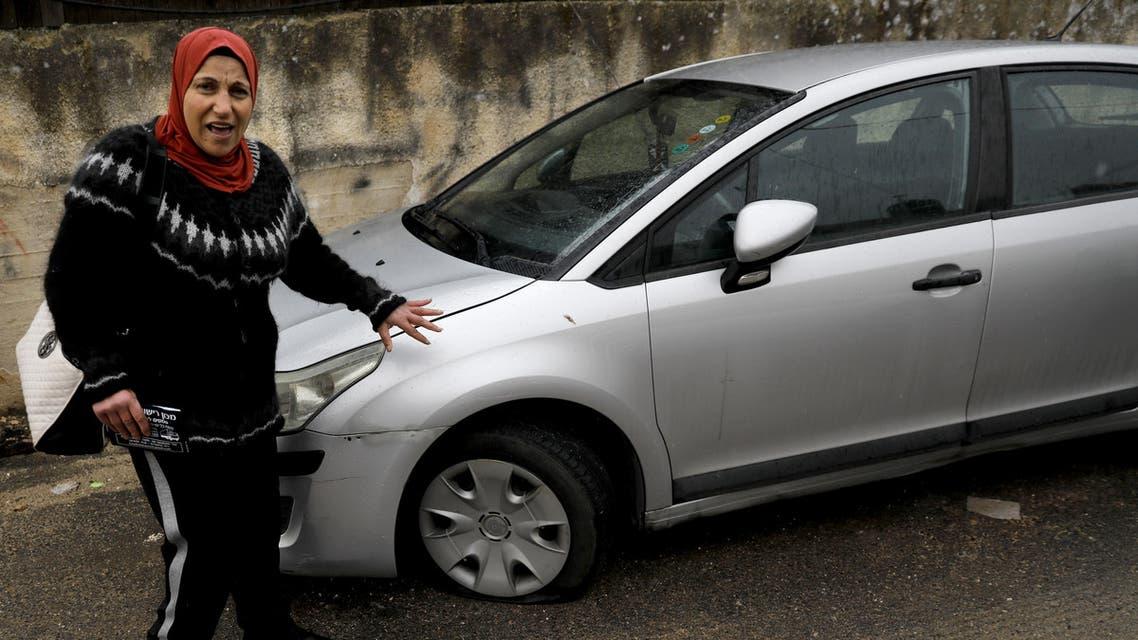 A Palestinian women displays her vehicle's slashed tire in the Palestinian neighbourhood of Shuafat, neighbouring the Israeli settlement of Ramat Shlomo, in Israeli annexed east Jerusalem, on December 9, 2019. (AFP)