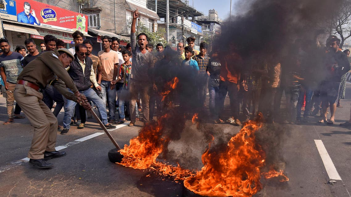 A policeman removes burning tires set ablaze by demonstrators during the strike to protest against Citizenship Amendment Bill (CAB), a bill that seeks to give citizenship to religious minorities persecuted in neighbouring Muslim countries, in Guwahati, India, December 10, 2019. (Reuters)