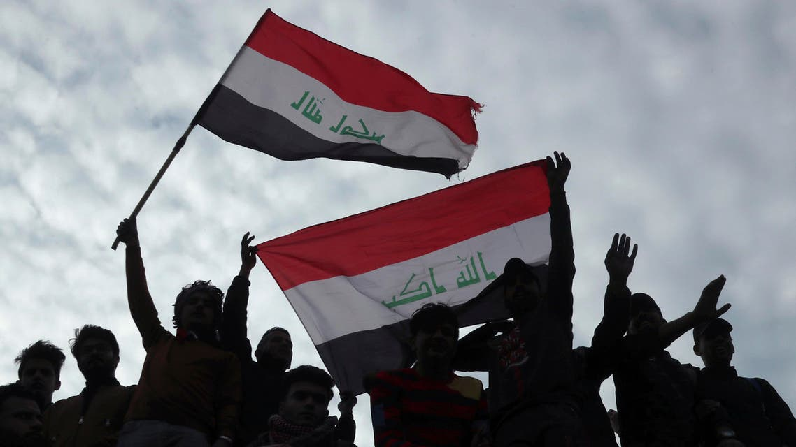 Protesters chant anti government slogans and fly Iraqi flags during minor clashes with Iraqi riot police, at a bridge in Baghdad, Iraq, Tuesday, Dec. 10, 2019. (AP)