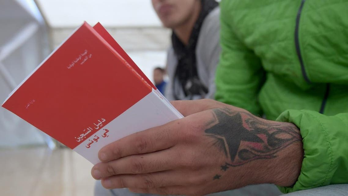 A prisoner holds booklets distributed by Tunisian officials and intended for all inmates and prison guards in Tunisia, that inform them about human rights in a simplified manner, in Mornaguia prison near the capital Tunis on December 10, 2019. (AFP)