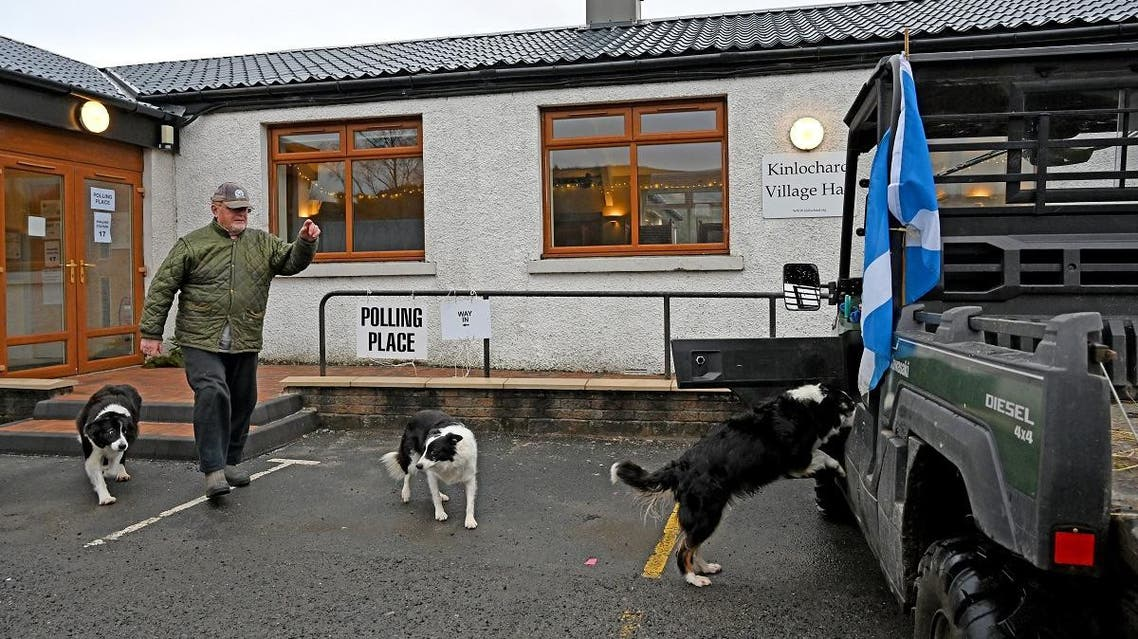 A Scottish Saltire flag hangs from a vehicle as man and his dogs leave Kinlochard Village Hall, serving as a polling station, in Kinlochard, Scotland. (AFP)