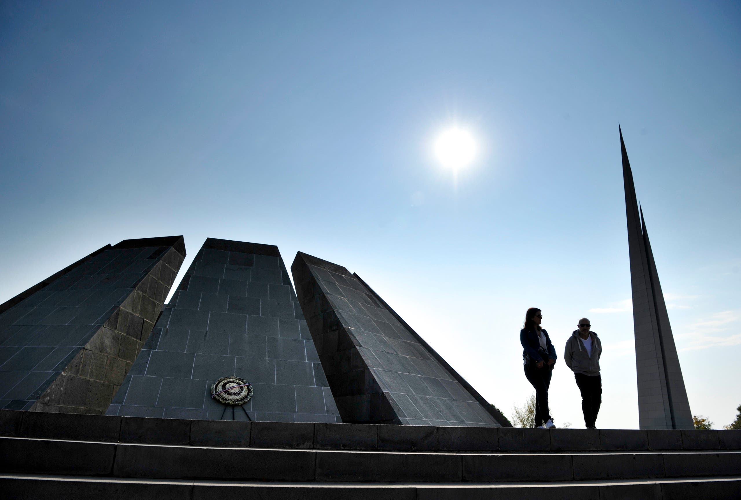 A couple walk at the Tzitzernakaberd memorial to the victims of mass killings by Ottoman Turks, in the Armenian capital Yerevan on Oct. 30, 2019. (AP)