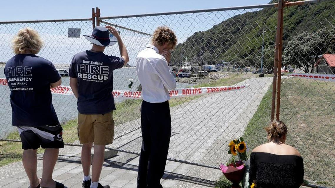 People lay flowers at a fence on the waterfront in Whakatane, New Zealand, Tuesday, Dec. 10, 2019. A volcanic island in New Zealand erupted Monday Dec. 9 in a tower of ash and steam while dozens of tourists were exploring the moon-like surface, killing multiple people and leaving many more missing. (AP Photo/Mark Baker)