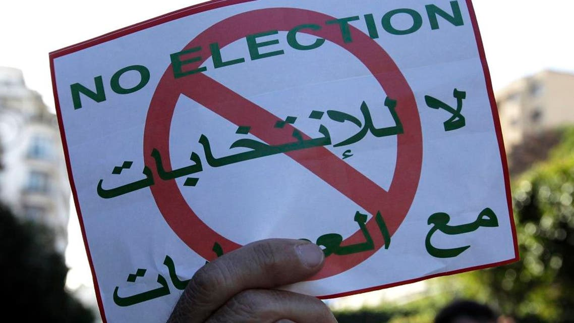 People demonstrate with anti-election posters in Algiers. (Photo: AP)