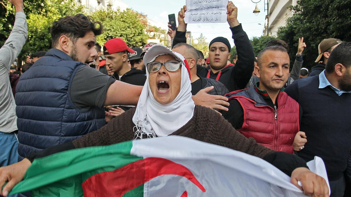 An Algerian woman chants slogans as she waves a national flag while taking part in an anti-government demonstration in the capital Algiers on December 12, 2019 (AFP)