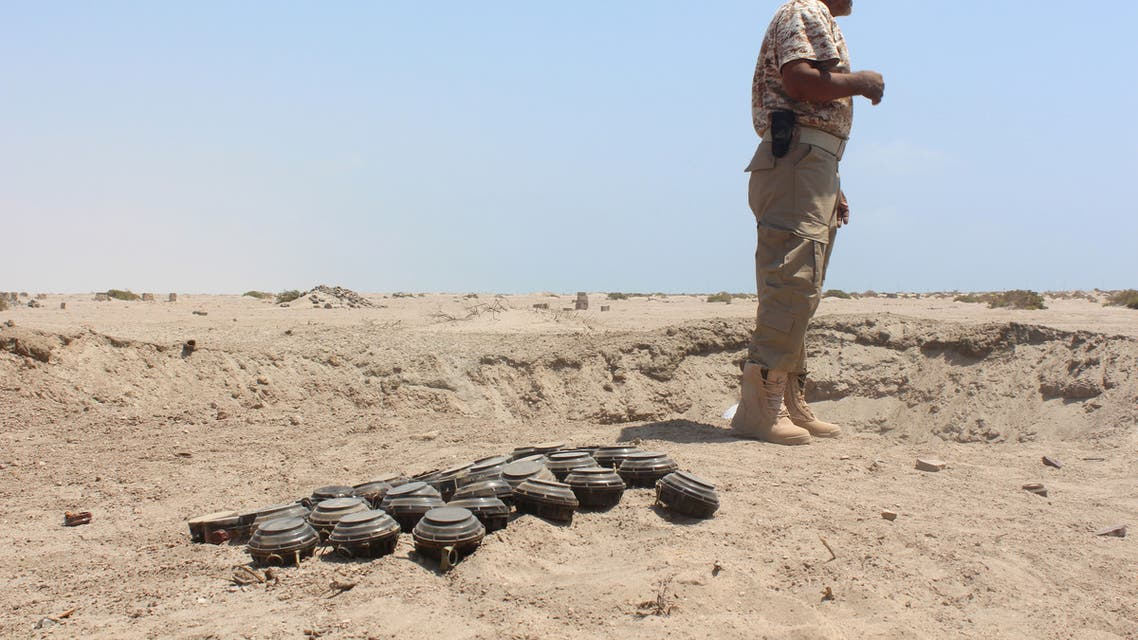 A Yemeni security forces member stands next to unexploded ordnance confiscated from the Shiite Huthi rebels and militant extremists, as he prepares to neutralise the mines and explosives in the desert of al-Alam, east of the southern port city of Aden, on March 10, 2016. Al-Qaeda in the Arabian Peninsula, the jihadist network's powerful Yemeni affiliate, has taken control of some parts of the country and a local branch of the Islamic State (IS) group has also emerged as a new threat. Al-Qaeda and IS jihadists have stepped up attacks in Aden despite the efforts of the government and its backers in a Saudi-led coalition battling the Huthis and their allies to secure it.
