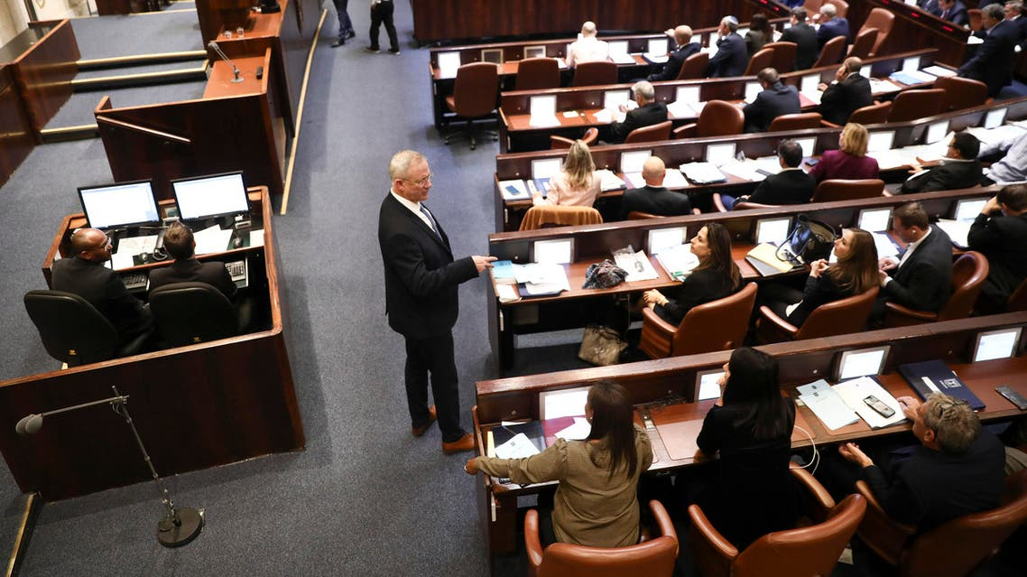 Blue and White party leader Benny Gantz, center, stands during a Knesset session in Jerusalem, Wednesday, Dec. 11, 2019. (AP)
