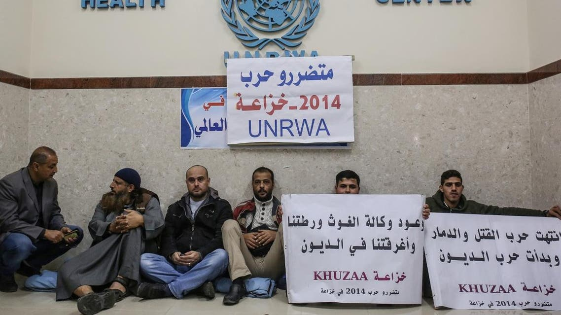 Palestinian protesters hold placards calling on the United Nations Relief and Works Agency (UNRWA) to pay them for the repair of their homes, damaged during the 2014 Israel–Gaza conflict. (AFP)