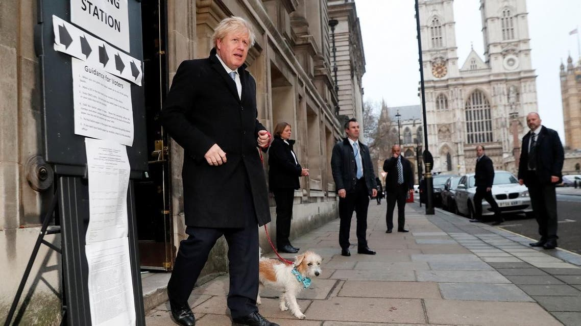 Britain's Prime Minister Boris Johnson leaves with dog Dilyn at a polling station, at the Methodist Central Hall, after voting in the general election in London. (Reuters)