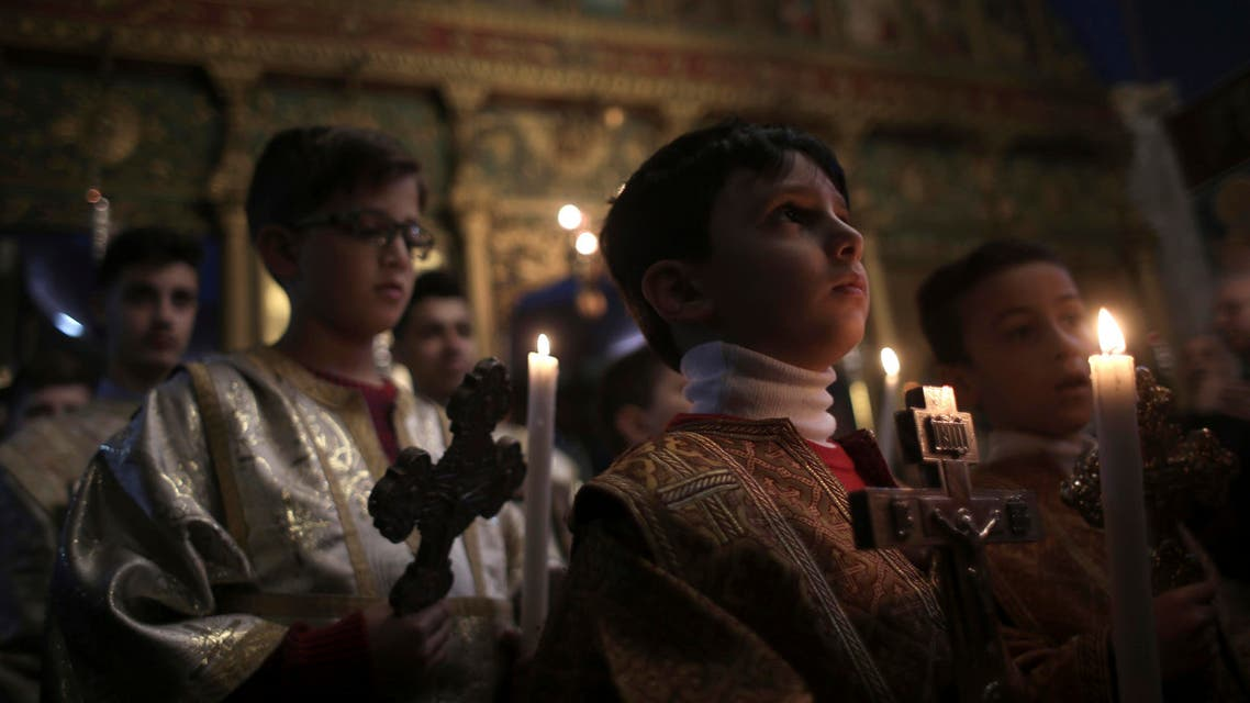 Palestinian Greek orthodox Christians attend the Christmas Eve Mass at St. Porphyrios Church in Gaza City, early Sunday, Jan. 7, 2018. (AP Photo)