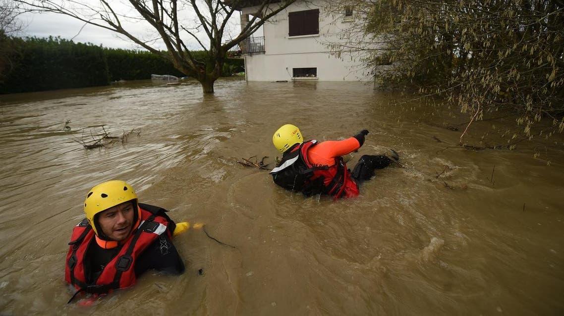 Firefighters inspect a flooded neighbourhood following heavy rains in Peyrehorade, southwestern France, on December 14, 2019. (AFP)