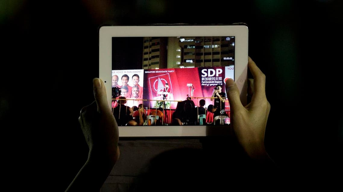A supporter records the final rally for the opposition Singapore Democratic Party ahead of the Sept. 11 general elections in Singapore. (File photo: AFP)