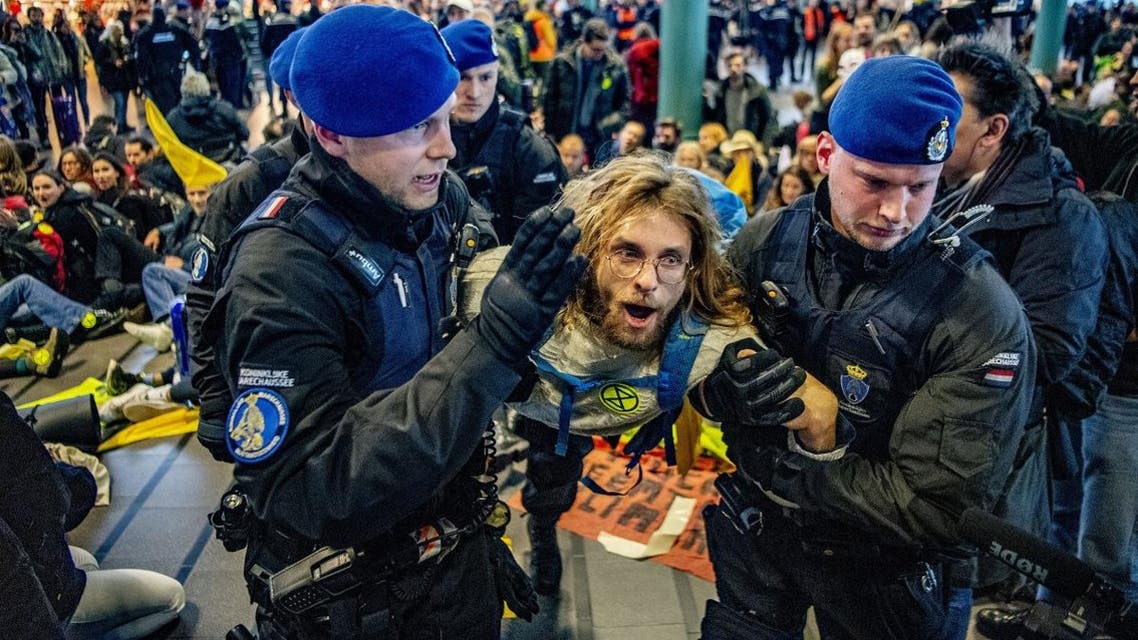 Royal Dutch police officers escort a Greenpeace activist during a protest to denounce airline pollution in the main hall of the Amsterdam Schiphol airport on December 14, 2019. (AFP)