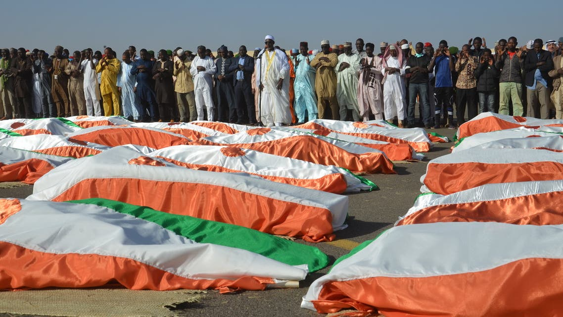 The Imam of the Great Mosque of Niamey, Cheikh Djabir Ismaël(C), who led the funeral prayer, stands in front of the bodies of military personnel at the Niamey Airforce Base in Niamey, on December 13, 2019. 71 Military personnel died in an attack on a military camp in Inates in the western Tillaberi region on December 10, 2019.