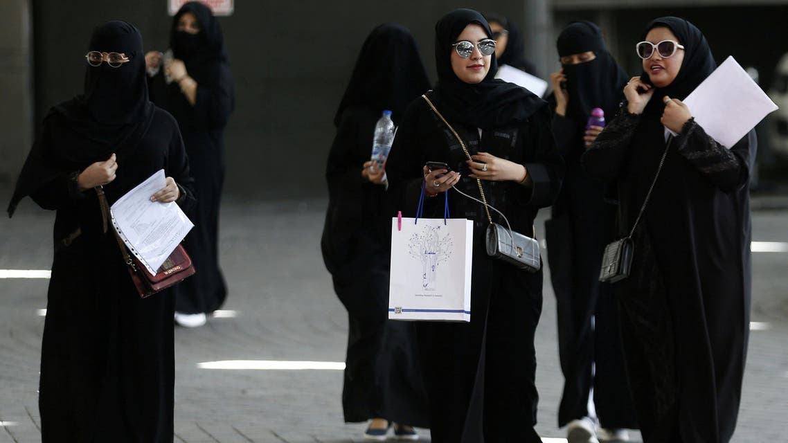 Saudi students walk at the exhibition to guide job seekers. reuters