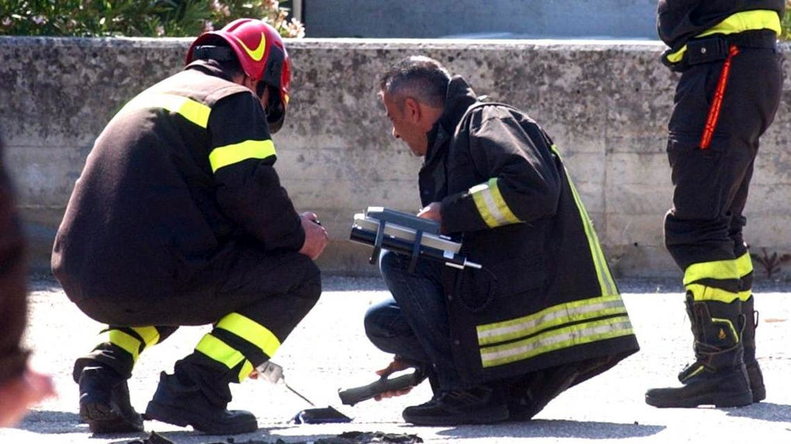 """Italian firefighters inspect the site where an explosive device blasted outside """"Francesca Morvillo Falcone"""" high school in Brindisi, Italy, Saturday, May 19, 2012 (AP)"""