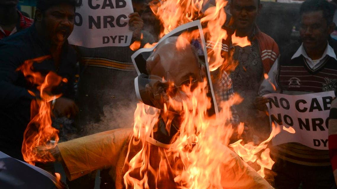 Indian left wing activists of Democratic Youth Federation of India (DYFI) shout slogans as they burn an effigy of India's Home Minister Amit Shah during a demonstration against the Indian government's Citizenship Amendment Bill in Siliguri. (AFP)