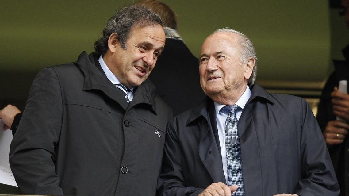 """Michel Platini (L) and Jpseph """"Sepp"""" Blatter (R) talk before a match at Stamford Bridge in London on May 23, 2013. (File photo: AFP)"""