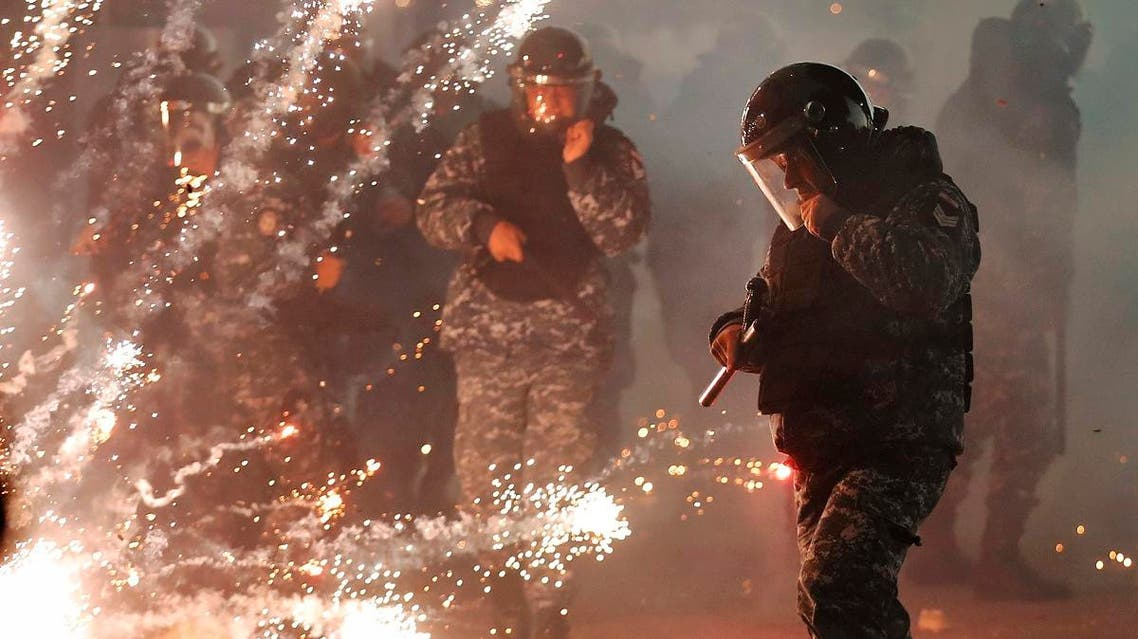 Lebanese riot policemen run from firecrackers that fired by the supporters of the Shiite Hezbollah and Amal Movement groups, as they try to attack the anti-government protesters squares, in downtown Beirut, on December 14, 2019. (AP)