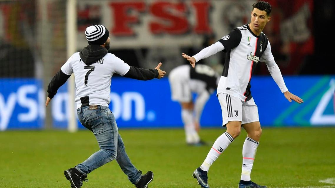 A man invades the pitch and runs to hug Juventus' Cristiano Ronaldo during the Champions League Group D soccer match against Bayer Leverkusen at the BayArena in Leverkusen, Germany. (AP)