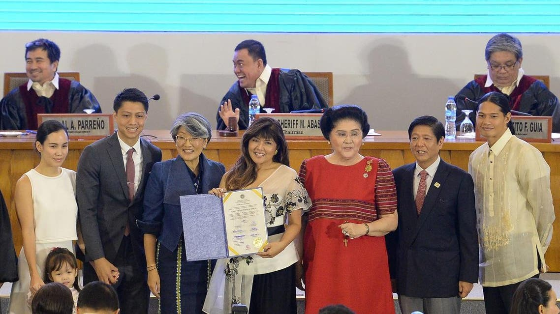 Philippine Senator-elect Imee Marcos (C), daughter of the late dictator Ferdinand Marcos, poses with family members, Irene Marcos (3rd L), former first lady Imelda Marcos (3rd R, in red), and former senator Ferdinand marcos jnr (2nd R) during the proclamation ceremony by the Commission on elections in Manila on May 22, 2019. (AFP)