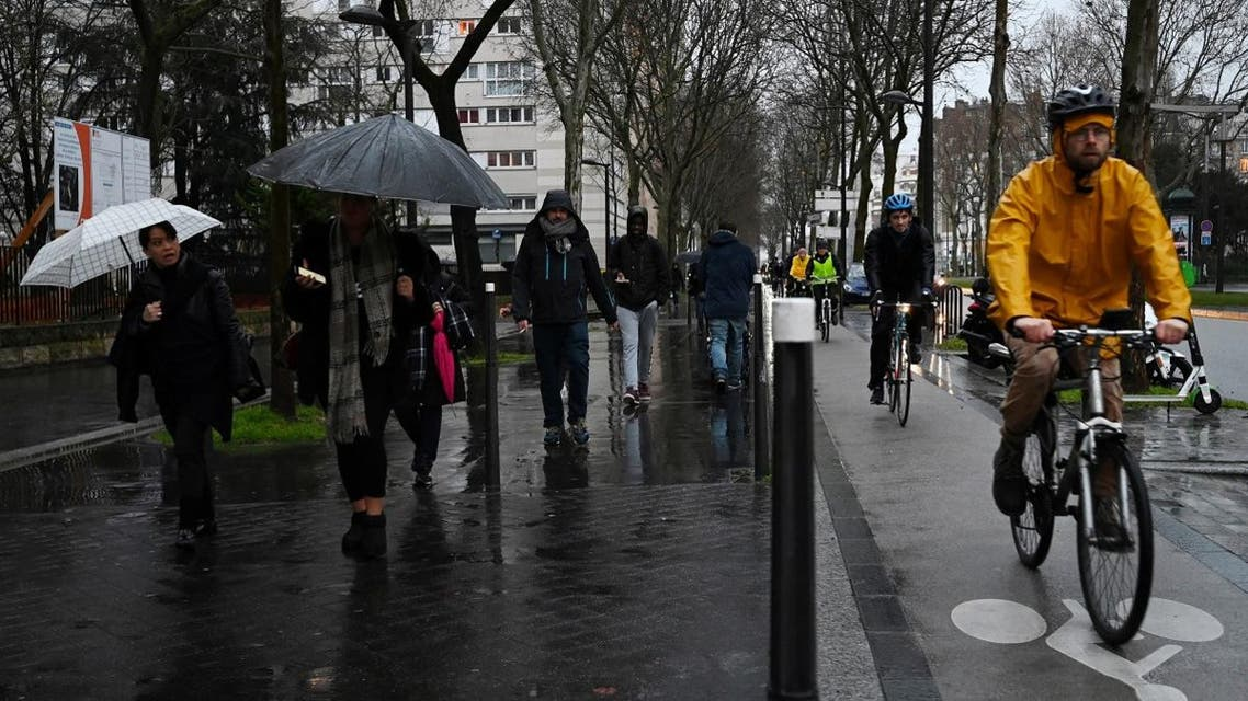 People ride bicycles and walk in the rain in Porte de Vanves in Paris, on December 16, 2019, during a strike of Paris' public transports operator RATP and of the French state railway company. (AFP)