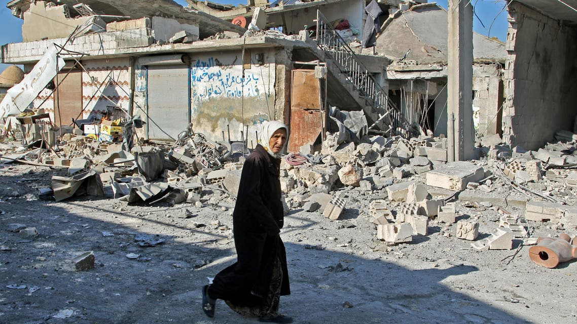 A Syrian woman walks past destruction at the site of a reported government bombardment in the village of Maasaran on the outskirts of Maaret al-Numan in Syria's northwestern Idlib province on December 17, 2019. Abdulaziz KETAZ / AFP