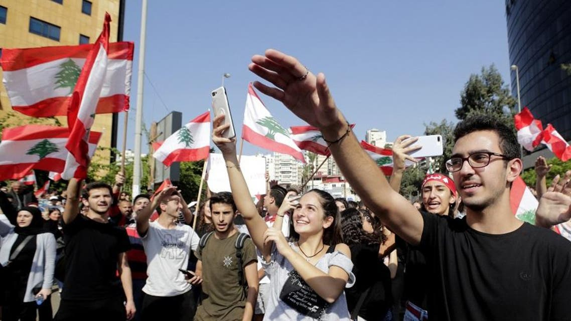 Lebanese students from various schools wave national flags and shout slogans as they gather in front of the Ministry of Education. (File photo: AFP)