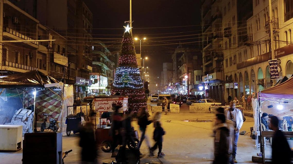Pedestrians walk past a Christmas tree installed in Tripoli's Al-Nour Square at the entrance of the northern Lebanese costal city on December 11, 2019. (AFP)
