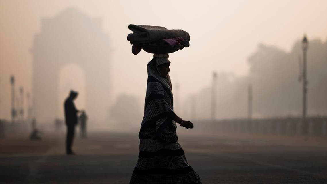 A woman balances a load on her head as she crosses a street near India Gate in heavy smoggy conditions in New Delhi. afp