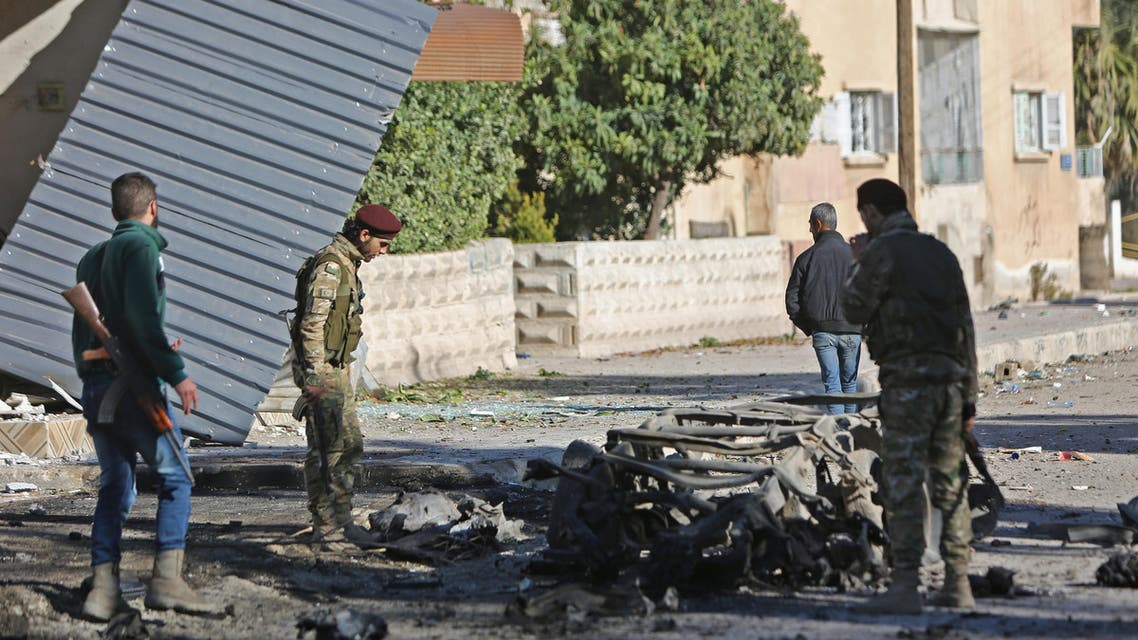 Turkish-backed Syrian fighters stand at the scene of a car bomb explosion in the centre of the town of Ras al-Ain, along the border with Turkey in the northeastern Hassakeh province, on December 4, 2019. Nazeer Al-khatib / AFP