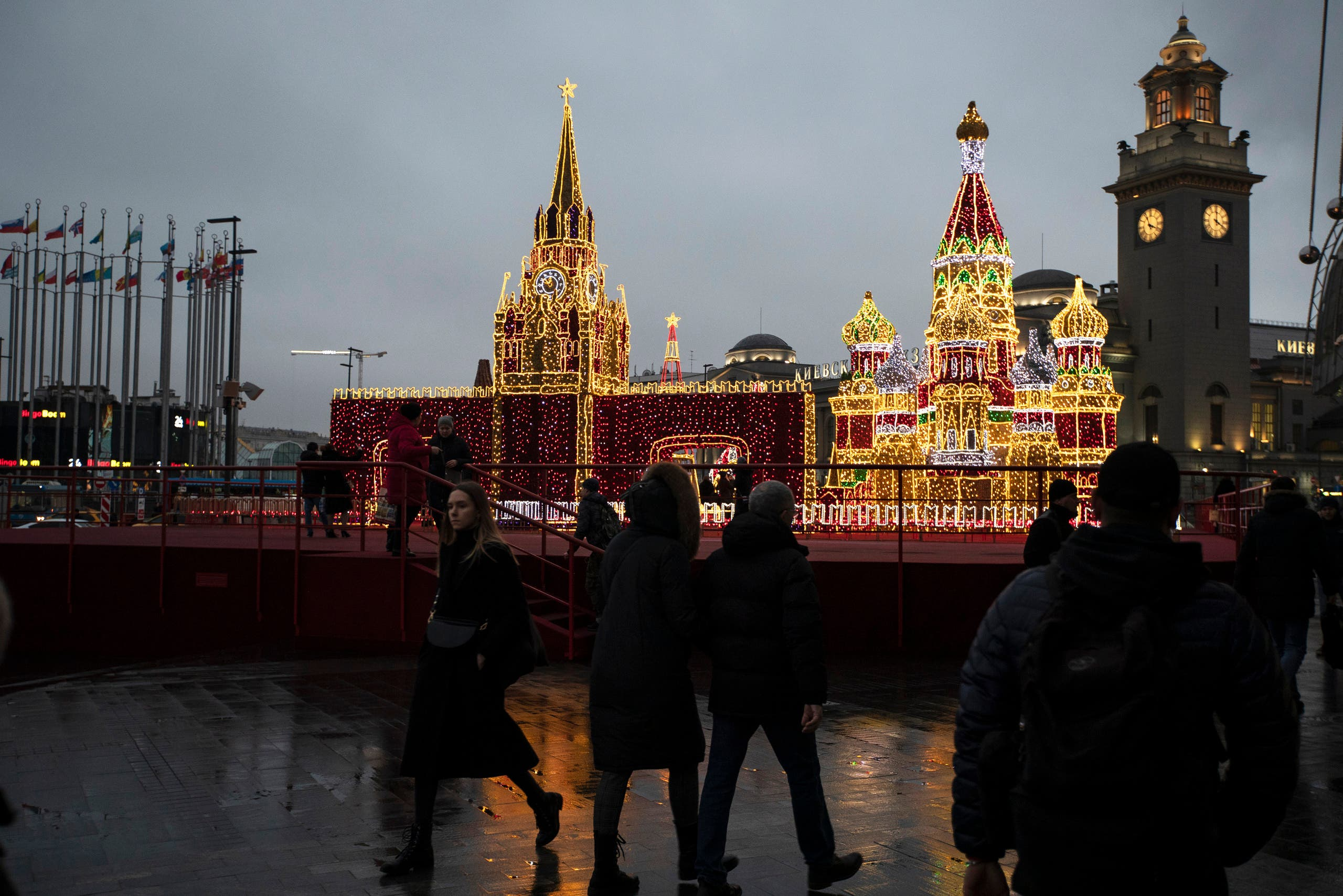 People pass models of St. Basil Cathedral, center right, and Kremlin's Spasskaya tower in Square of Europe decorated for New Year and Christmas celebrations in Moscow, Russia in Moscow, Russia, Wednesday, Dec. 18, 2019. (AP Photo/Pavel Golovkin)