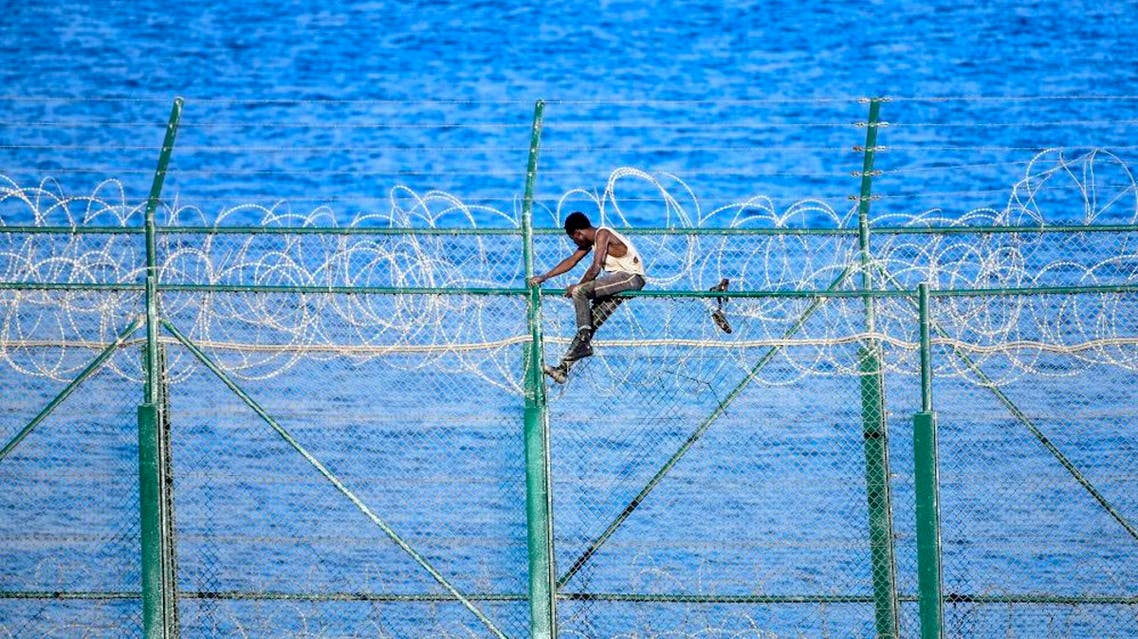 A migrant forces his way into the Spanish territory of Ceuta on August 30, 2019. (AFP)