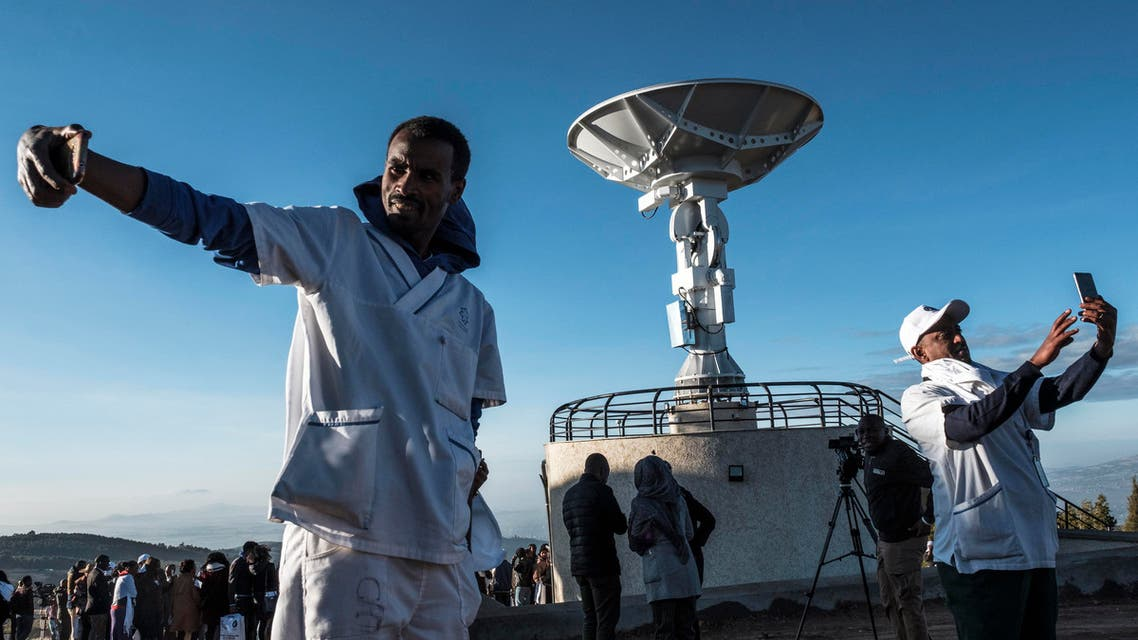 People take selfie pictures in front of a satellite antenna during the ceremony for the launching of the Ethiopian Remote Sensing Satellite (ETRSS) in Entoto Observatory and Research Centre in Addis Ababa, on December 20, 2019. Ethiopia launched its first satellite on December 20, 2019, a landmark achievement for the country's space programme that caps a banner year for the African space industry. The launch of the Ethiopian Remote Sensing Satellite (ETRSS) took place at a space station in China, though scores of Ethiopian and Chinese officials and scientists gathered at the Entoto Observatory and Research Centre outside the capital, Addis Ababa to watch a live broadcast. EDUARDO SOTERAS / AFP