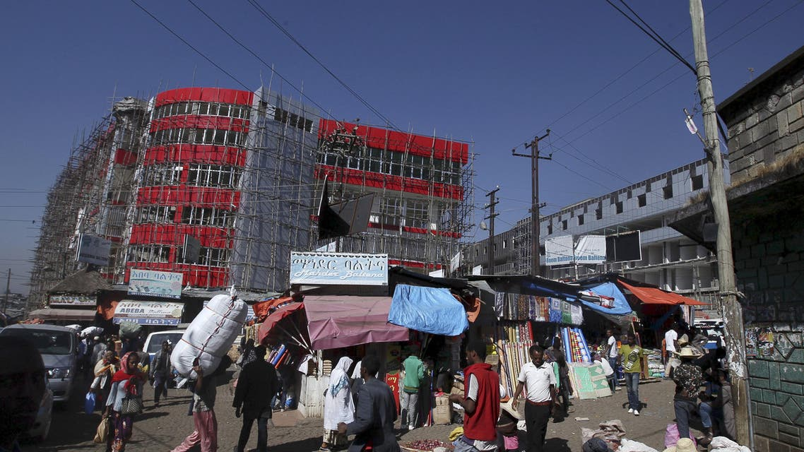 A new shopping centre under construction is seen behind old buildings and market stalls at the Mercato market in Addis Ababa November 18, 2015. Addis Ababa's 'Mercato' - Italian for 'market' - is reputedly the biggest open-air market in Africa, lying in the west of the capital. Supermarkets have sprouted across the city as the metropolis has expanded with Ethiopia's booming economy, but Mercato remains a popular destination for shoppers seeking clothing, electronics and a huge range of other items. It has been around for as long as the city, which was founded at the end of the 19th century, but it took its current form, and its name, from the Italians who invaded Ethiopia in 1935. The Italian occupation ended in 1941. Picture taken November 18, 2015. REUTERS/Tiksa Negeri
