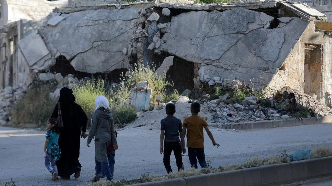 People walk near rubble of damaged buildings in the city of Idlib, Syria. (Reuters)