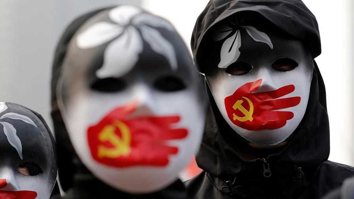 People wearing masks stand during a rally to show support for Uighurs and their fight for human rights in Hong Kong, Dec. 22, 2019. (Photo: AP)