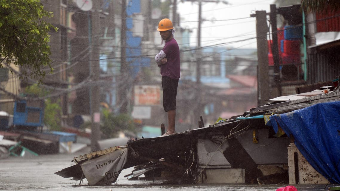 A resident stands on top of the roof of his submerged house as heavy rains brought about by Tropical Storm Fung-Wong flooded homes in Manila on September 19, 2014. Heavy rains brought y the outer bands of Tropical Storm Fung-Wong shut down the Philippine capital Manila on September 19, stranding motorists and forcing tens of thousands to flee their flooded homes, officials said. (AFP)