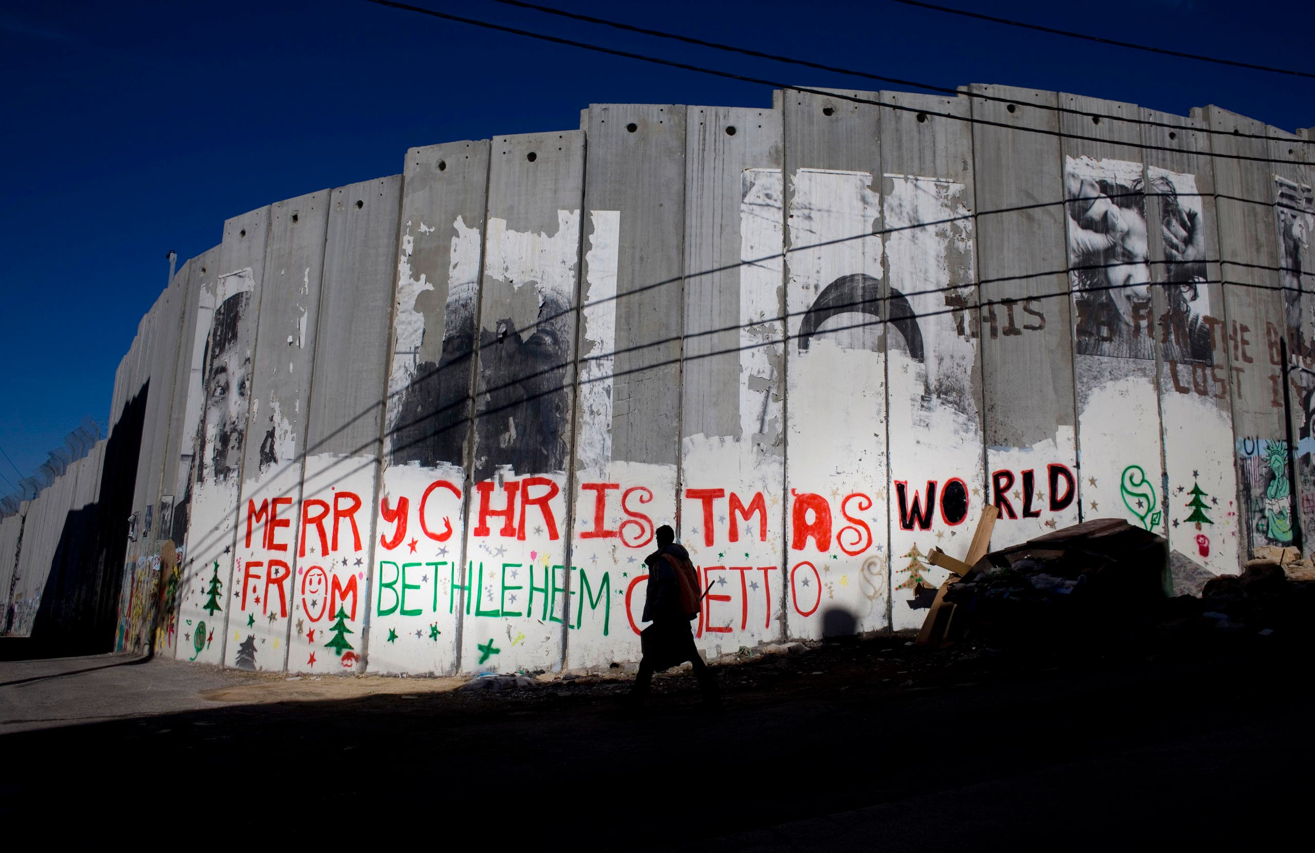 A Palestinian man walks past a portion of Israel's separation barrier in Bethlehem in December 2010. (File photo: AP)